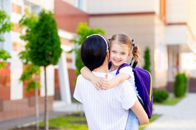 Pierwszego dnia szkoły, pierwszego dnia jesieni, mama niesie na rękach małą uczennicę do pierwszej klasy, koncepcja wraca do szkoły