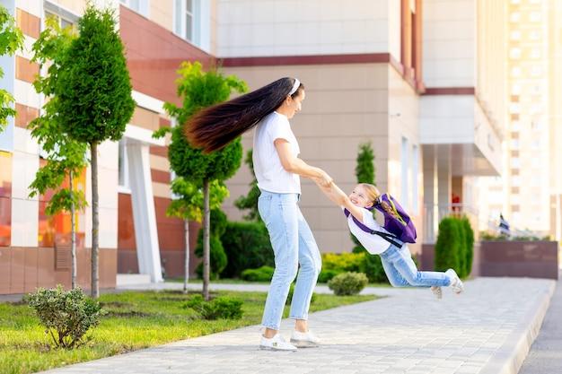 Pierwszego dnia w szkole matka rodzica radośnie okrąża dziewczynkę do uczennicy z plecakiem za ręce prowadzące do pierwszej klasy, koncepcja powrotu do szkoły