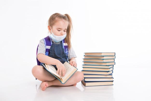 Pierwszoklasista uczy się czytać. mała dziewczynka o nauczaniu na odległość w domu. dziecko w masce medycznej czyta książkę. uczeń odrabia lekcje.
