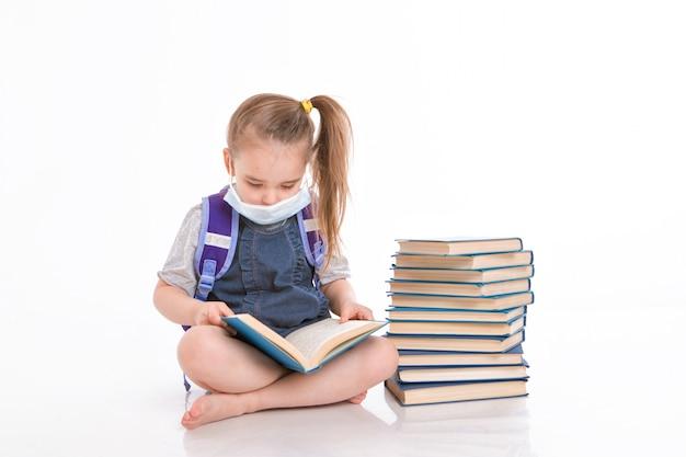 Pierwszoklasista uczy się czytać. mała dziewczynka w kształceniu na odległość w domu. dziecko w masce medycznej czyta książkę.