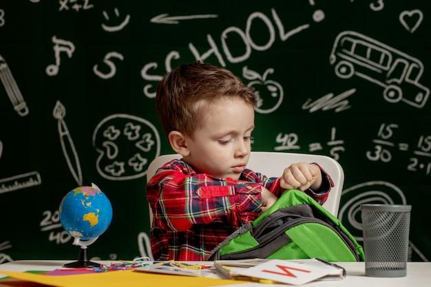 Pierwszy dzień szkoły. mały chłopiec ze szkoły podstawowej. powrót do szkoły. mały chłopiec zbiera szkolny plecak do szkoły. dziecko ze szkoły podstawowej