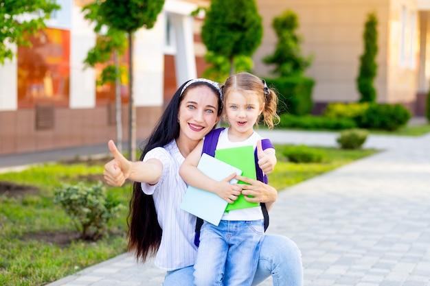 Pierwszy dzień szkoły, matka i córka uczennicy pokazują klasie kciuki do góry, rodzic prowadzi dziewczynę do pierwszej klasy, koncepcja wraca do szkoły