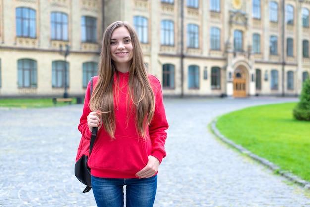 Pierwszy dzień w nowej koncepcji prywatnego instytutu. zdjęcie optymistycznej uroczej, inteligentnej, inteligentnej dziewczyny stojącej przed budynkiem