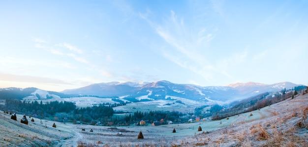 Pierwszy jesienny przymrozek na pastwisku ze stogami siana i wschodem słońca w górskiej wiosce. dwa ujęcia ściegu obrazu.