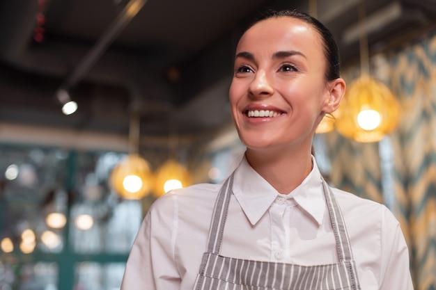 Pierwszy klient. portret marzycielskiej wesołej miłej kelnerki pozowanie na niewyraźne tło i uśmiechając się, patrząc na bok