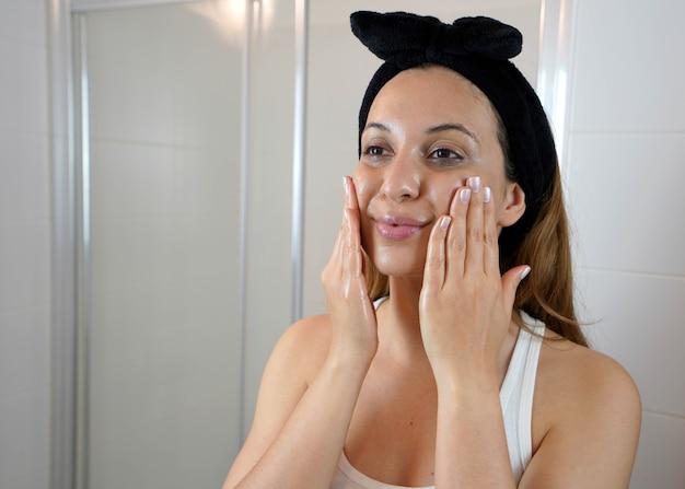 Pierwszy krok to demakijaż olejkiem oczyszczającym. piękna młoda kobieta za pomocą ekologicznego olejku oczyszczającego do demakijażu bez wacika.