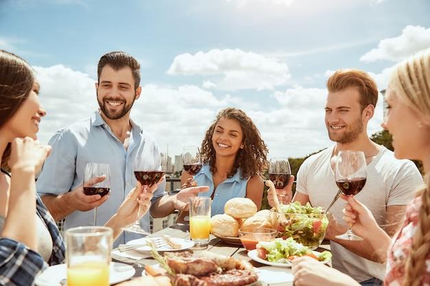 Pierwszy letni grill grupa szczęśliwych młodych ludzi je świeże jedzenie, rozmawiając i pijąc