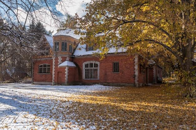 Pierwszy śnieg i żółte liście wokół starego wiktoriańskiego domu w carskim siole