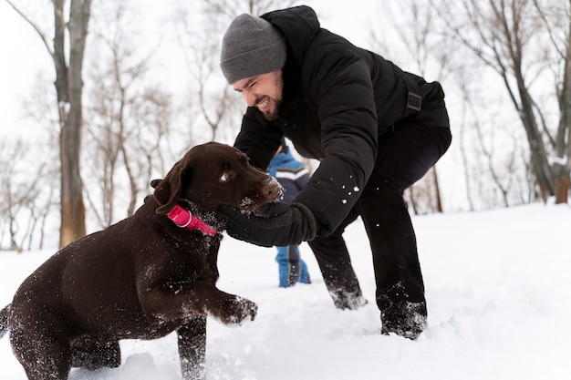 Pies bawi się z dzieckiem na śniegu z rodziną
