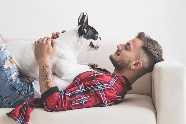 Pies buldog francuski z czułym nastawieniem ze swoim właścicielem ubranym w kraciastą koszulę leżącą na kanapie