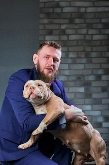 Pies bulli i jej właściciel, jej kochający mistrz, który trzyma psa w ramionach, obejmuje i całuje. pies czuje się dobrze na rękach właściciela