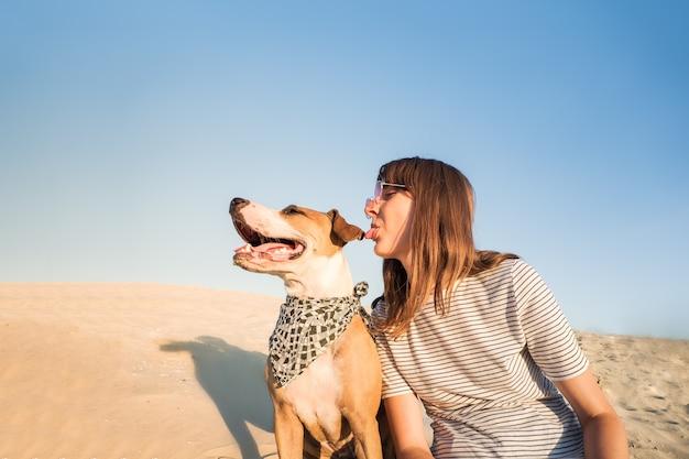 Pies i człowiek śmieją się, udając najlepszych przyjaciół. zabawna osoba płci żeńskiej i szczeniak staffordshire terrier siedzieć na piasku w gorący letni dzień