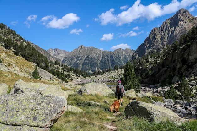 Pies i kobieta piesze wędrówki w parku narodowym aigón estortes i estany de sant maurici.