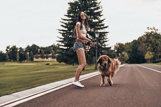 Pies ją uszczęśliwia! pełna długość pięknej młodej kobiety bawiącej się z psem i uśmiechającej się podczas spędzania czasu na świeżym powietrzu