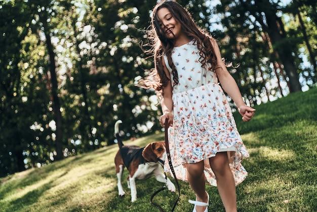 Pies jest zawsze w pobliżu. śliczna mała dziewczynka bawi się z psem i uśmiecha się podczas spaceru na świeżym powietrzu
