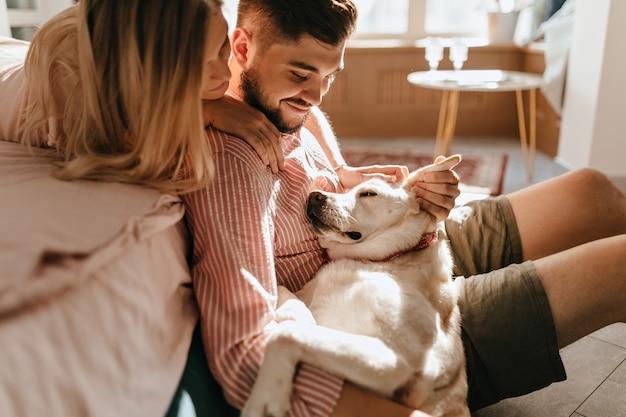 Pies leży na nogach właściciela. mężczyzna w różowej koszuli i jego ukochana kobieta podziwiają swojego białego zwierzaka.