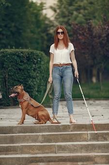 Pies przewodnik pomaga niewidomej kobiecie w parku