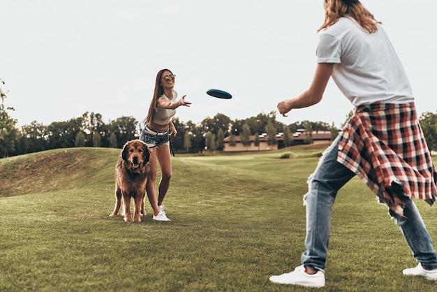 Pies przynosi im radość. pełna długość pięknej młodej pary rzucającej plastikowym dyskiem podczas zabawy z psem na zewnątrz