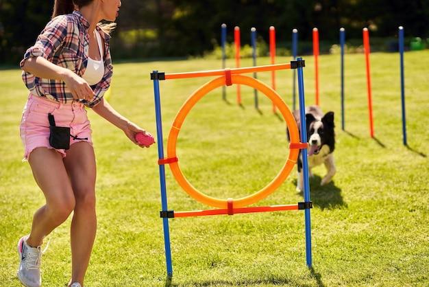 Pies rasy border collie i kobieta na polu agility