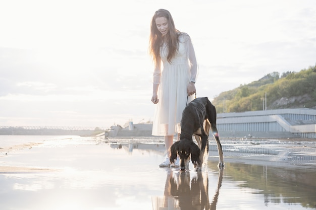 Pies saluki pije wodę z kałuży z uśmiechniętą kobietą