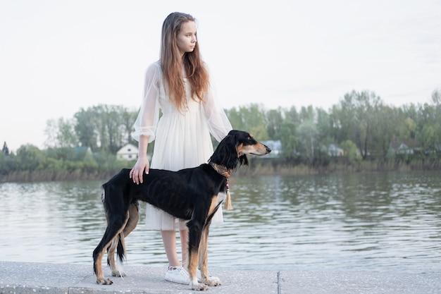 Pies saluki stojący z atrakcyjną młodą kobietą w pobliżu brzegu rzeki z bliska portret