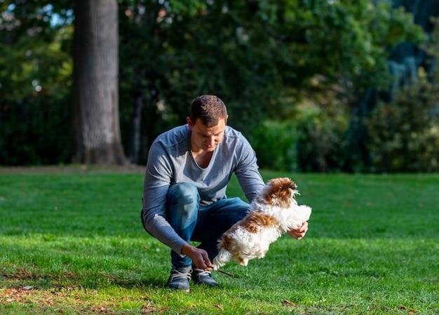 Pies skaczący nad kijem, bariera zespołowa, mężczyzna bawi się z psem