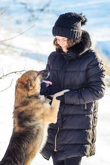 Pies stoi na tylnych łapach w pobliżu dziewczynki i patrzy na jej twarz podczas zimowego spaceru