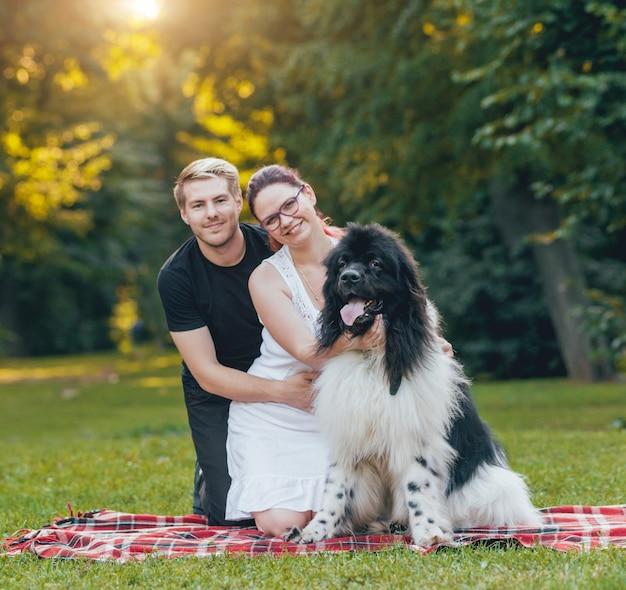 Pies z nowej funlandii bawi się z mężczyzną i kobietą w parku