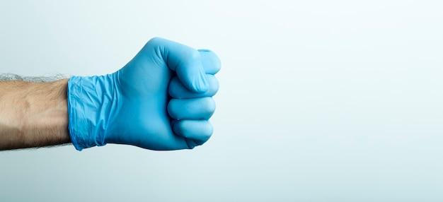 Pięść w rękawicy medycznej. ręka lekarza w niebieskiej rękawicy medycznej na jasnym tle.