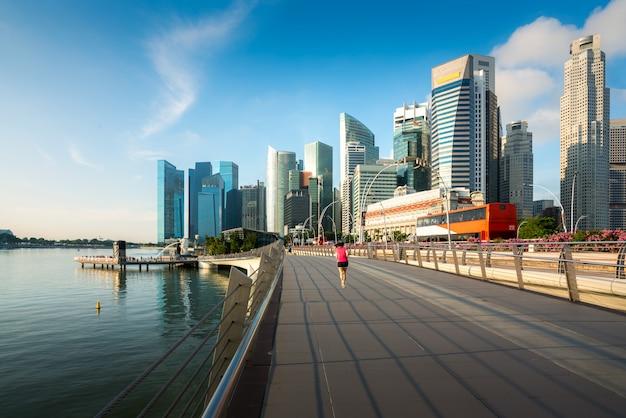 Piesi chodzą wzdłuż mostu blisko marina zatoki w singapur z singapur drapaczem chmur w tle