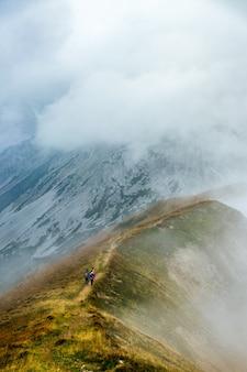 Piesi wspinający się po górskim szlaku