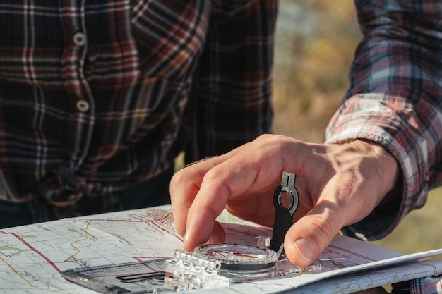 Piesze wycieczki hobby turystyka zbliżenie męskiej dłoni za pomocą kompasu i mapy