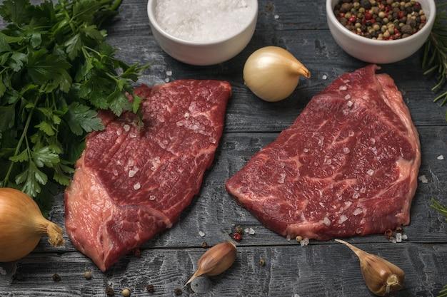 Pietruszka, cebula, przyprawy i steki wołowe na czarnym stole.