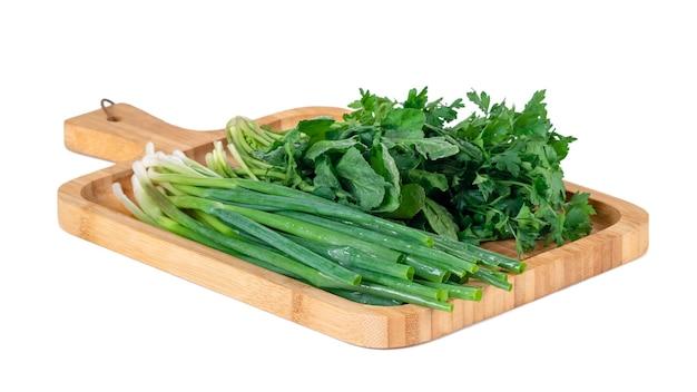 Pietruszka, cebula szparagowa i rzeżucha na desce na białym tle. warzywo.
