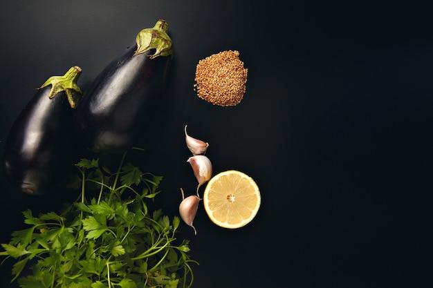 Pietruszka, czosnek, cytryna, sezam i dwa świeże bakłażany na czarnym tle