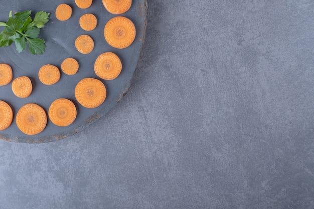 Pietruszka i pokrojona w plasterki marchew deska, na marmurowym tle.