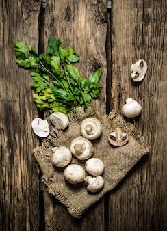 Pietruszka i świeże grzyby. na drewnianym tle.