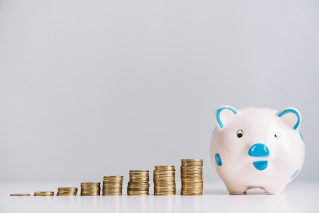 Piggybank i rosnące monety na biurku odblaskowym