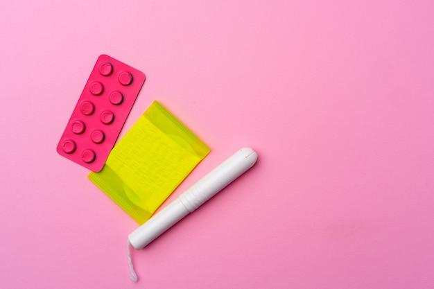 Pigułki antykoncepcyjne, podpaski higieniczne i tampony na różowym tle