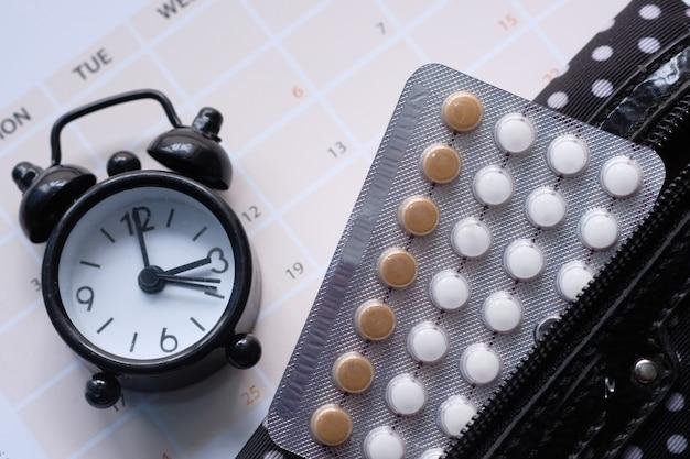 Pigułki antykoncepcyjne, zegar i kalendarz, z bliska.