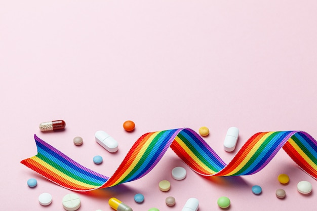 Pigułki hormonalne po zmianie płci. przejście transpłciowe. transwestyta. pride lgbt tęczowa wstążka i pigułki na różowo.