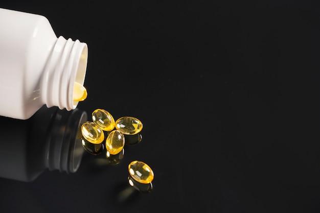 Pigułki i biała butelka lekarstwa leżą na lustrzanym czarnym tle, które jest w nim odzwierciedlone.
