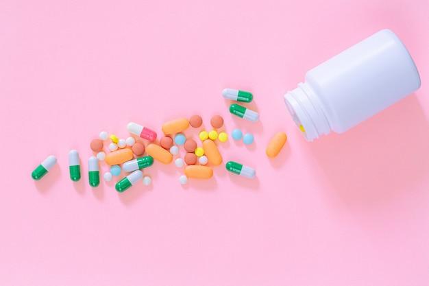 Pigułki i butelki na pigułki na różowym tleróżne pigułki farmaceutyczne