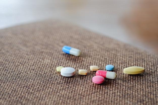 Pigułki i kapsułki ułożone na brązowym tle. pojęcie opieki zdrowotnej.