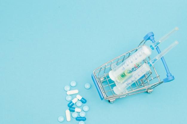 Pigułki i wózek na zakupy na niebieską ścianą. kreatywny pomysł na koncepcję kosztów opieki zdrowotnej, apteki, ubezpieczenia zdrowotnego i firmy farmaceutycznej. skopiuj miejsce