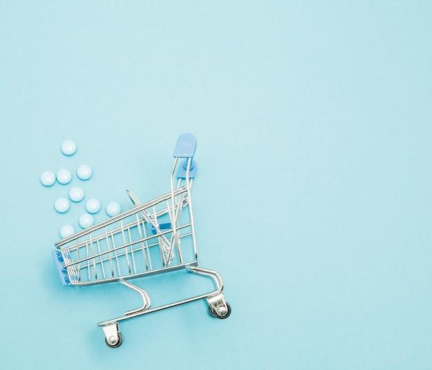 Pigułki i wózek na zakupy na niebieskim tle. kreatywny pomysł na koszt opieki zdrowotnej