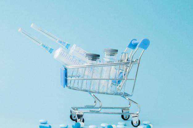 Pigułki i zastrzyk medyczny w wózku na zakupy