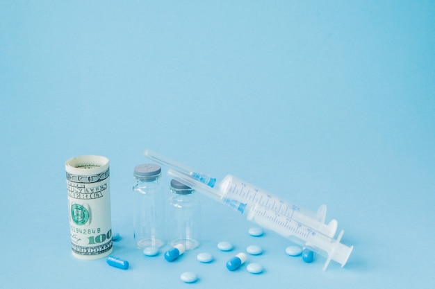 Pigułki i zastrzyki medyczne na niebieskim tle. kreatywny pomysł na koszt opieki zdrowotnej, aptekę, ubezpieczenie zdrowotne i koncepcję biznesową firmy farmaceutycznej.