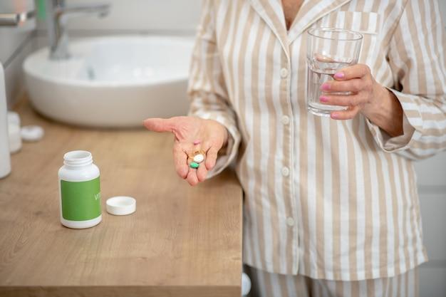 Pigułki. kobieta w piżamie biorąc jej poranne tabletki