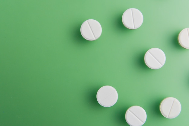 Pigułki, leki, leki, tabletki w kolorze białym, rozpakowane na zielonym tle z głębokimi cieniami. leżał płasko.